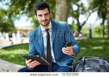 Handsome young businessman sitting at park, using mobile and tablet.