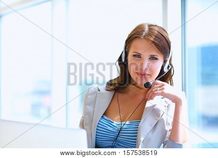 Businesswoman talking on the phone while working on her computer at the office.