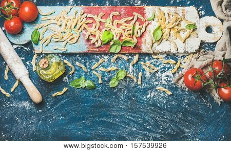 Ingredients for cooking Italian dinner. Fresh pasta casarecce, cherry-tomatoes, basil leaves, olive oil on colorful wooden board over dark blue background. Top view, copy space. Food frame concept