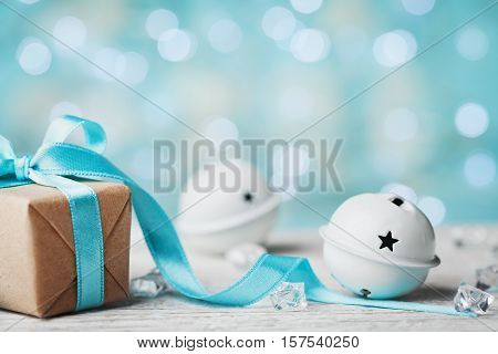 Christmas gift box and white jingle bell against turquoise bokeh background. Holiday greeting card.