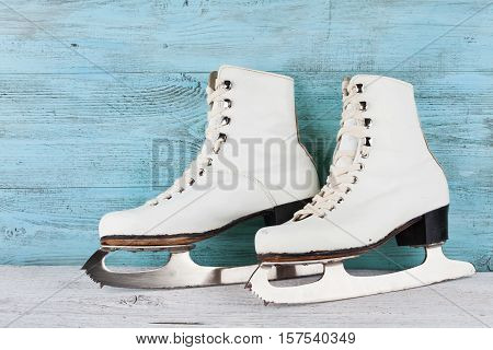 Vintage ice skates for figure skating on turquoise background.