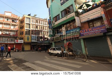 KATHMANDU NEPAL - NOV 06 2016: Nepali people walking down the Thamel street under sunrise in the morning in Kathmandu Nepal