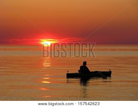 A kayaker watches a beautiful sunset on the peaceful waters of Lake Superior.