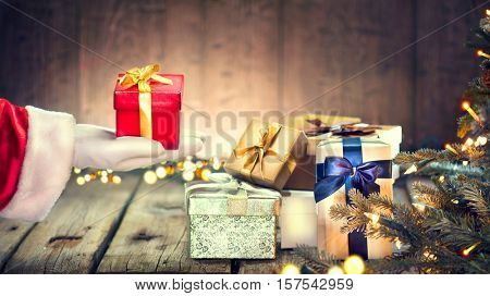 Santa Claus hand holding Christmas Gift box over wooden background. Decorated Christmas tree with Winter Holiday Gifts.