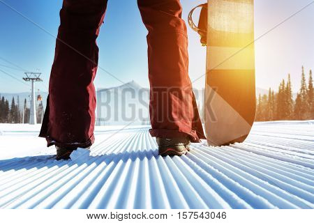 Snowboarder stands on slope backdrop. Closeup legs and snowboard