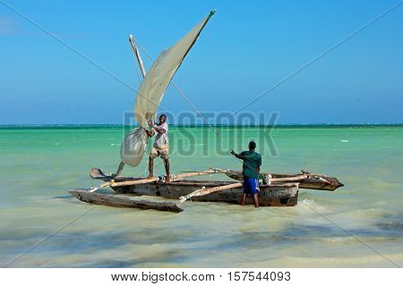 ZANZIBAR - OCTOBER 28, 2014: Unidentified men launching a wooden sailboat (dhow) on the clear turquoise water of Zanzibar island