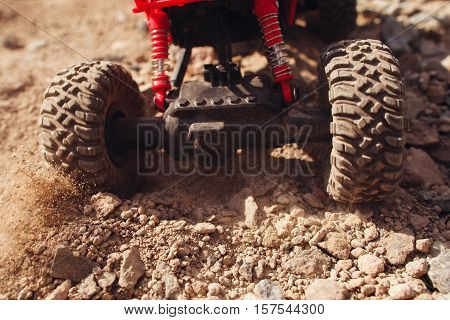 Toy car skidding on dry landscape, close-up. Photo of suv wheel slipping on rocky road, pillar of dust out of tyre. Extreme rally, buggy concept