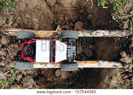 Top view on rc car above yawner on logs. Small crawler overcoming pit on handmade bridge. Extreme, offroad, entertainment concept