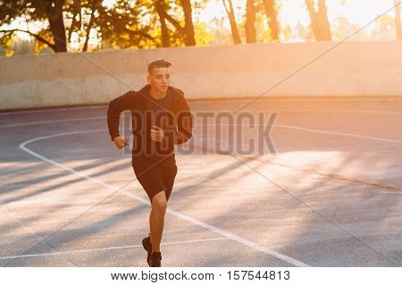 Evening jog of professional athlete, sunset light. Young sprinter training on open-air stadium, free space for text. Backdrop for motivational poster, success, going to aim concept