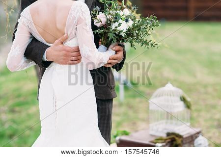 Just married couple dancing valse outdoor, free space. Bride and groom hugs, blurred green grass background. First wedding dance concept