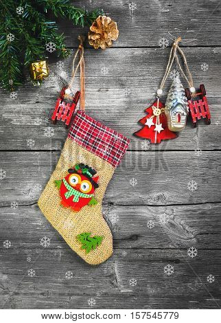 Christmas sock for presents. Christmas decoration stocking and toys hanging over gray rustic wooden background. The socks of burlap Christmas sweets gifts cakes. Snowflakes. Top view