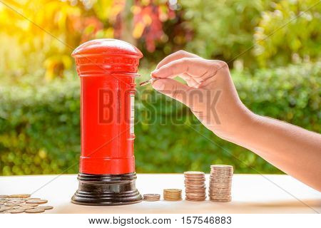 Woman putting coin into piggy bank in postbox shape
