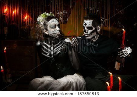 Portrait of a dead couple. Skeleton giving a light from candle to his woman with mouthpiece
