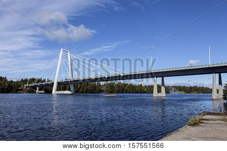 Modern bridge crosses a river. Construction in concrete and steel. Pylon and wires. Summer.