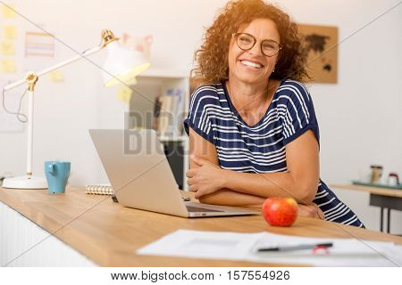 Successful middle aged woman smiling at her office