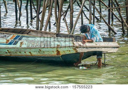 Omadal Island,Semporna,Sabah-Sept 10,2016:Sea Gypsy fishermen repairing the fisherman boat in Omadal Island,Semporna,Sabah.Fisherman is the main occupation for villagers