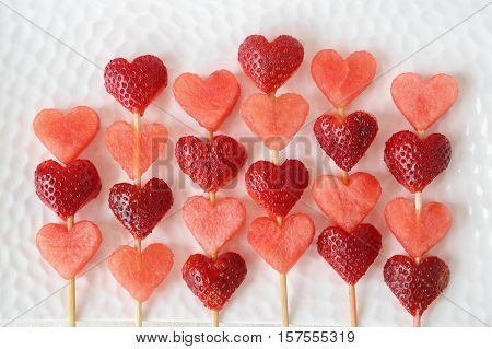 heart shape strawberry and watermelon fruit skewers on white plate fun food art for Valentines day