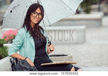 Asian girl city portrait. Woman smiling and sitting on bench outside with umbrella in casual business suite. Beautiful young mixed race Asian Caucasian woman.