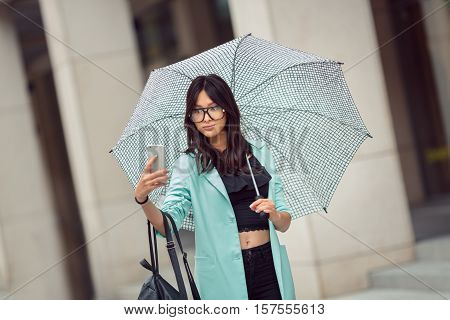 Travel Vacation Tourist Girl Selfie. Woman in casual suit glasses and umbrella taking self-portrait photo on city street or video chating.
