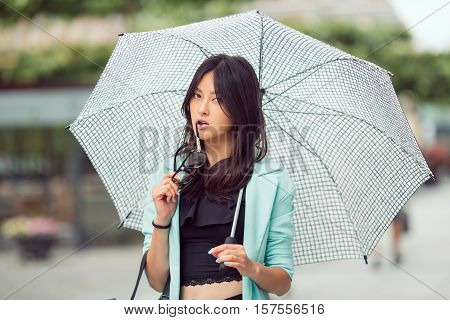 Confident asian girl city portrait. Serious sexy woman outside with umbrella and glasses in casual business suite looking at camera. Beautiful young mixed race Asian Caucasian woman.