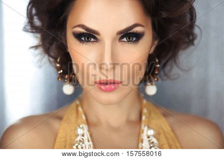 Beautiful woman with evening make-up and curly hair and yellow dress with jewelry pearls. Smoky eyes. Fashion portrait photo. Picture taken in the studio over bokeh shiny circles background.