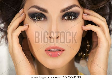 Beautiful woman with evening make-up and curly hair and yellow dress with jewelry pearls close-up. Smoky eyes. Fashion portrait photo. Picture taken in the studio over bokeh shiny circles background.