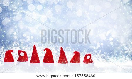 Seven christmas hats on a magical background