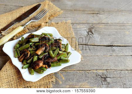 Delicious fried green beans with mushrooms and spices on a plate and on old wooden background with copy space for text. Warm green beans and mushrooms salad recipe. Easy vegetarian recipe
