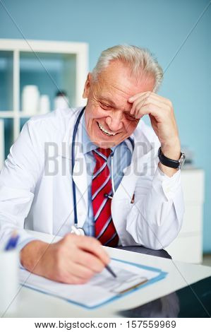 General practitioner sitting at table and smiling
