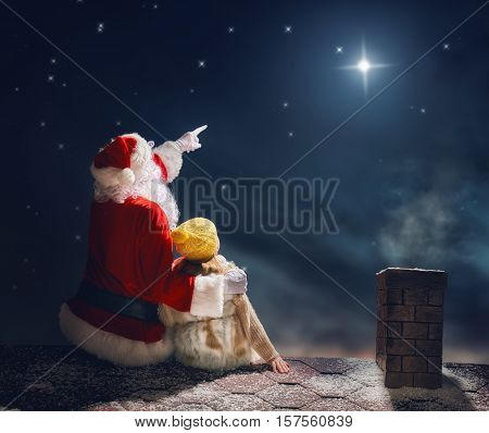 Merry Christmas and happy holidays! Cute little child girl and Santa Claus sitting on the roof and looking at Christmas star. Christmas legend concept.