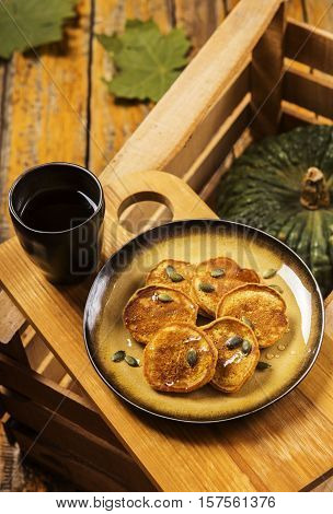 Pumpkin pancakes topped with honey and sprinkled with pumpkin seeds on a plate with the effect of craquelure on a wooden box with a cup of coffee and a bowl with honey. Selective focus