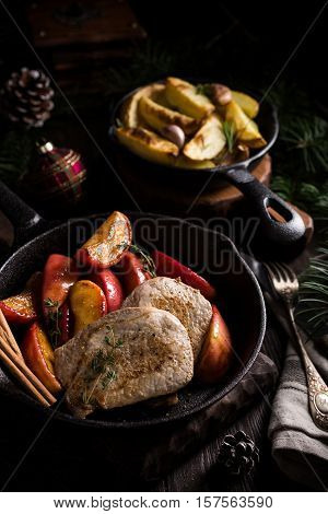 Delicious Christmas themed dinner table with roasted pork steak, caramelized apples and baked potatoes. Holiday concept.