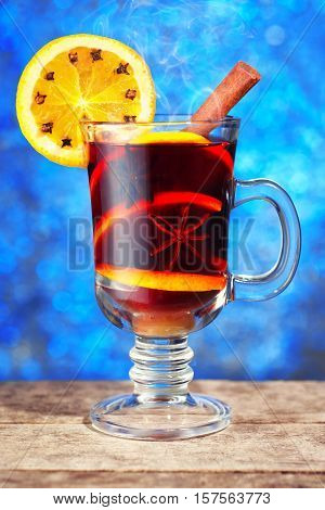 Hot mulled wine with cinnamon stick orange slice on wooden table with new year bokeh background. Christmas mulled wine with oranges and spices. Mulled wine on wooden planks in front of bright blue bokeh lights background. Mulled wine