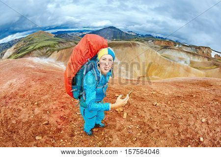 woman hiker photographer taking selfie on the rhyolite mountains background in Iceland. woman joking with a funny face and showing tongue