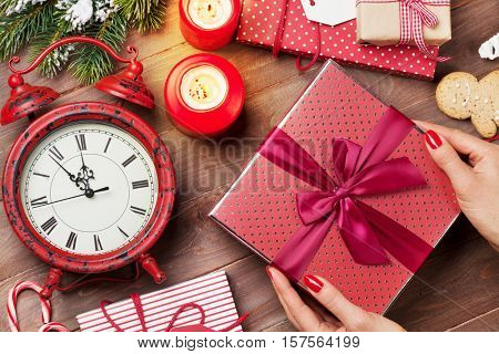 Female hands holding christmas gift above wooden table. Top view. Xmas gift wrapping