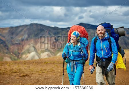 hikers on the trail in the Islandic mountains. hikers on the dark blue sky background. Trek in National Park Landmannalaugar, Iceland