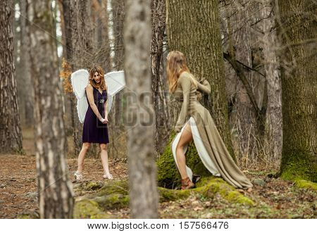 Two beautiful women in a fairytale forest. One as fairy with wings , the other is looking at her through the trees.
