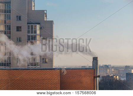 View of apartment house pipe with vapour at city background and blue sky