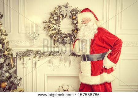 Happy Santa Claus standing by the fireplace and Christmas tree in a beautiful room, decorated for Christmas.