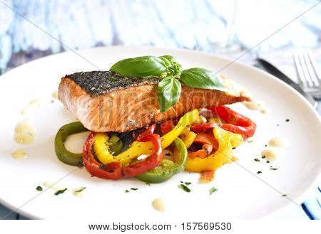 Delicious salmon filet with bel pepper vegetable and decorative basil leaf on a rustic wooden table. Healthy eating.