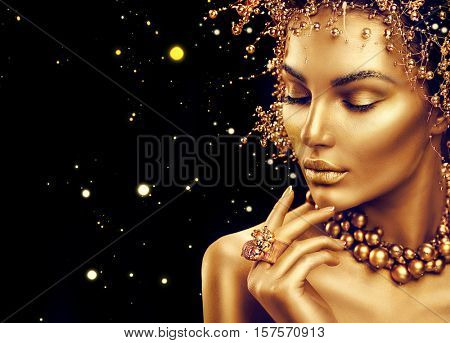 Gold Woman skin. Beauty fashion model girl with Golden make up, hair and jewellery on black background. Gold earrings, ring and necklace. Metallic, glance Fashion art portrait, Hairstyle and make up