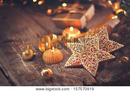 Christmas gingerbread cookies on wooden table decorated with garland and candles. Traditional Christmas food on old shabby wood, vintage styled