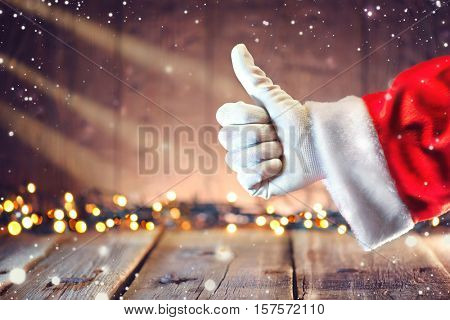 Santa Claus hand Thumb up gesture over Christmas holiday wooden rural background. Beautiful Empty Christmas room. New Year Background. Thumbup