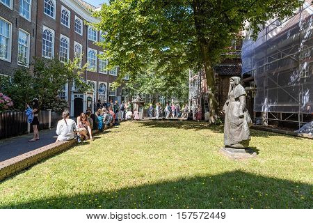 Amsterdam Netherlands - August 1 2016: Crowd in the Begijnhof. It is one of the oldest inner courts in the city of Amsterdam. A group of historic buildings centre on it.