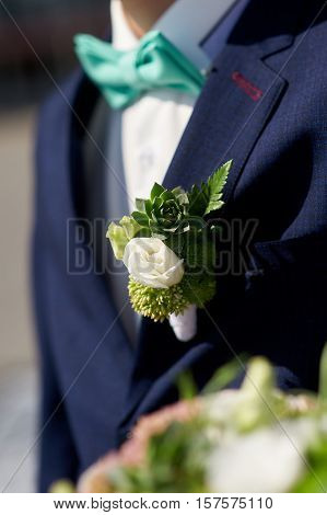 groom is with boutonniere and turquoise tie