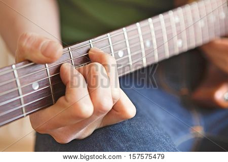 Man Strums Chord On Guitar