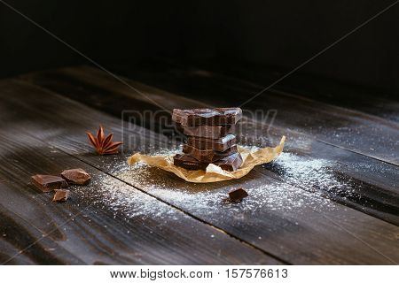 Chocolate on the black wooden table. Dark chocolate. Chocolate chunks