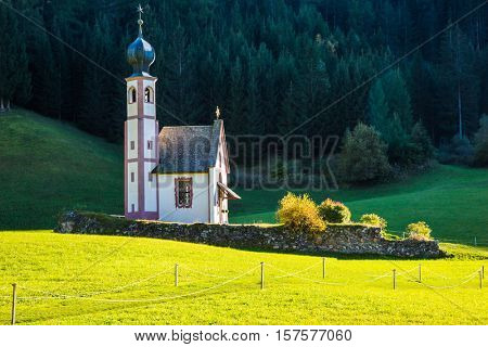 Tirol, Dolomites. The symbol of the valley Val di Funes - church of Santa Maddalena. Forested mountains surrounded by green Alpine meadows. Sunny warm autumn day
