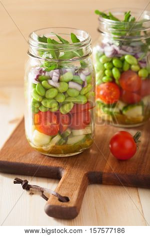 healthy vegetable salad in mason jar: tomato, cucumber, soybean, onion