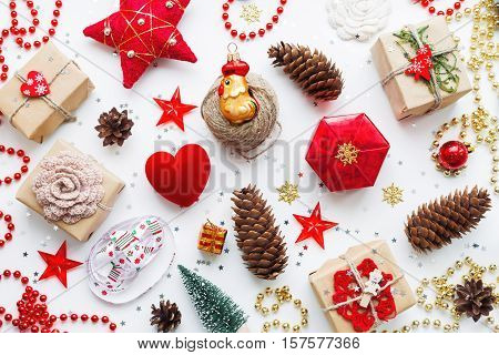 Christmas background with decorations. New Year 2017 symbol - Fire Rooster. Gifts in craft paper pine cones red hearts and confetti. Flay lay top view.